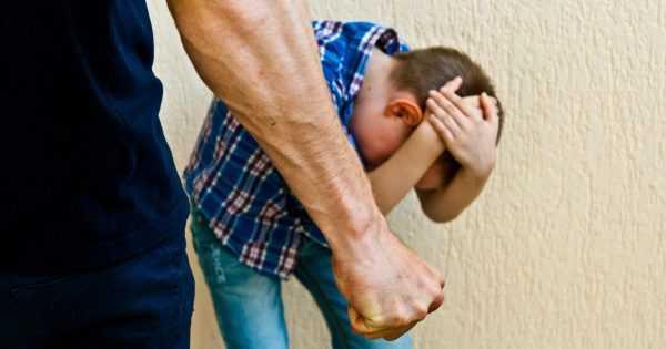 Ребёнок закрывает голову, прячась от сжатой в кулак мужской руки