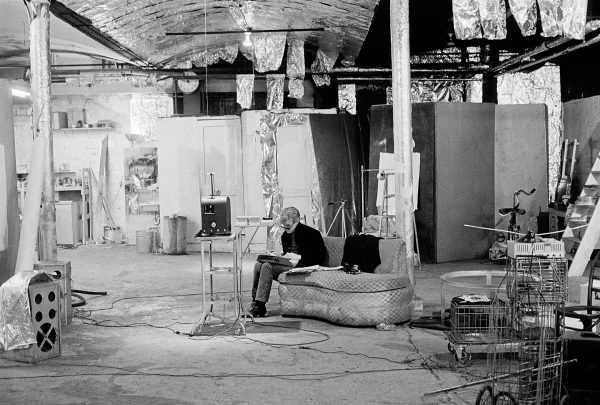Чёрно-белое фото: человек сидит посреди огромного производственного помещения