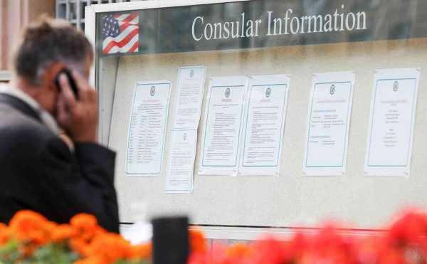 Мужчина с телефоном у доски объявлений с консульской информацией США
