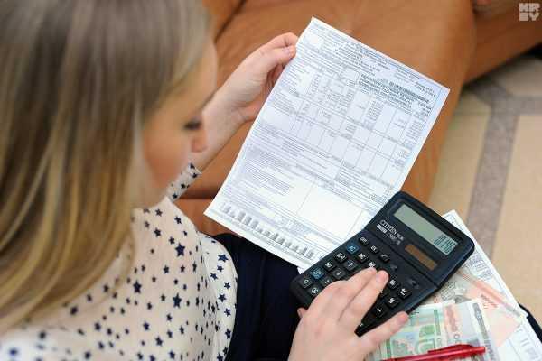 Женщина держит в руках квитанцию и калькулятор
