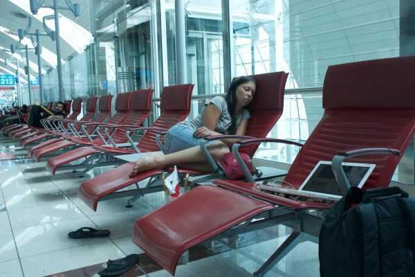 Девушка спит в аэропорту