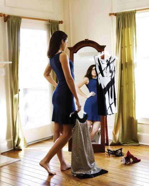 Девушка у зеркала меряет одежду