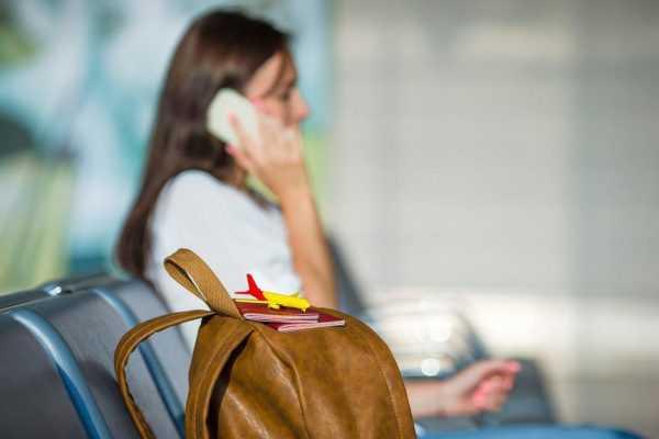 Женщина, сидя рядом с рюкзаком, разговаривает по телефону