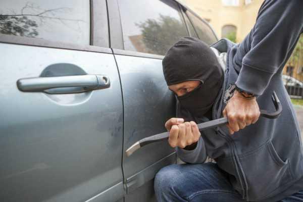 Человек в балаклаве с монтировкой у двери автомобиля