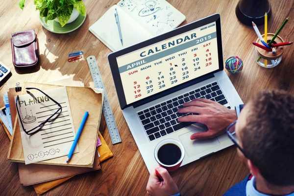 Мужчина работает за ноутбуком, на экране которого календарь