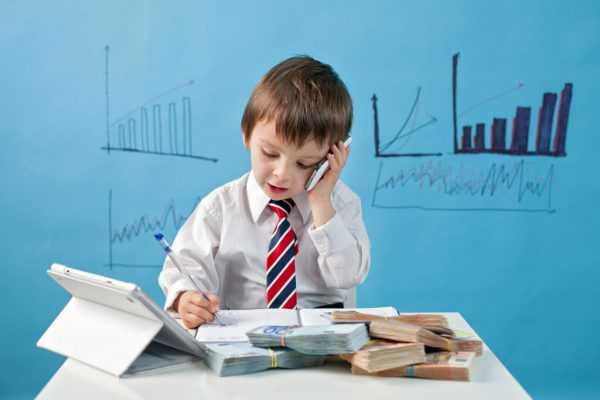 Мальчик с телефоном и ручкой сидит за рабочим столом