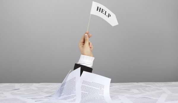 Рука в костюме с флажком «HELP» выглядывает из бумаг
