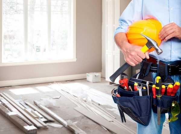 Рабочий с каской и набором инструментов в помещении, где делается ремонт