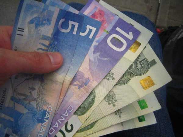 Канадские доллары в руке