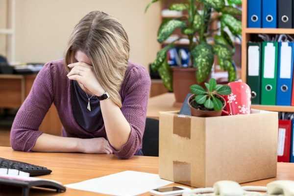 Женщина сидит за столом расстроенная