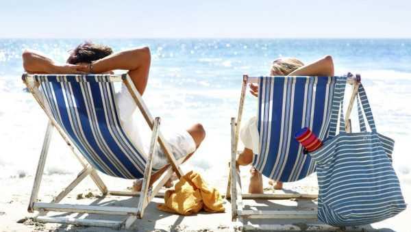 Мужчина и женщина лежат в шезлонге на пляже