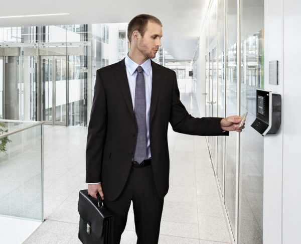 Мужчина подносит карточку к считывающему устройству