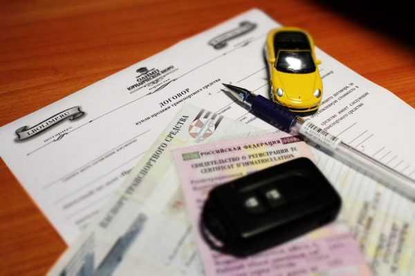 Игрушечный автомобиль и ручка на документах