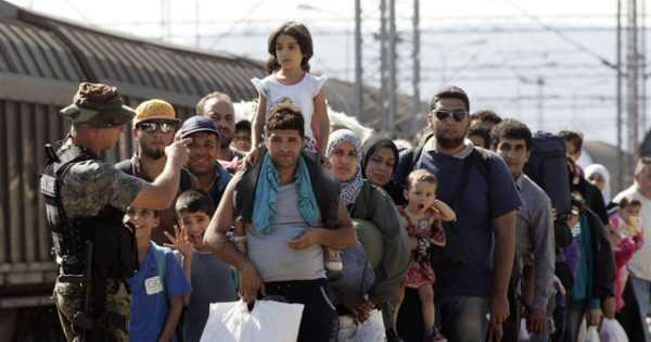 Беженцы в очереди и человек в военной форме