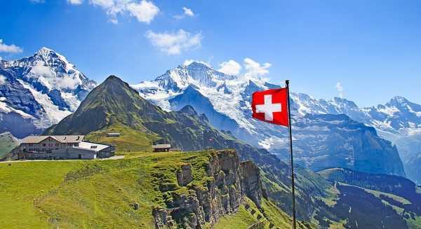 Швейцарский флаг на фоне гор