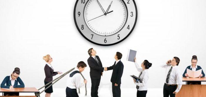 Сотрудники организации перед большими настенными часами