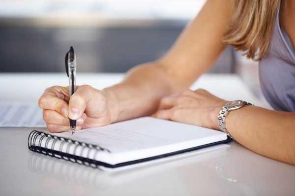 Женщина вносит записи в тетрадь
