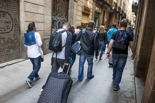 Люди с чемоданами идут по улице