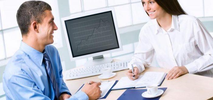 Мужчина и женщина располагаются за рабочим столом друг против друга