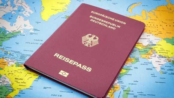 Паспорт гражданина Германии на фоне карты мира