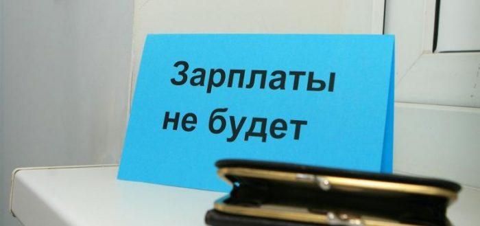 На столе лежит кошелёк и стоит табличка с надписью
