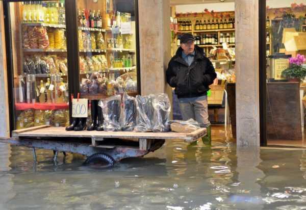 Мужчина рядом с затопленным магазином