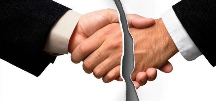 Разорванная пополам фотография, на которой изображено рукопожатие между двумя мужчинами