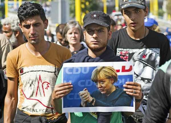 Мигранты с портретом Ангелы Меркель