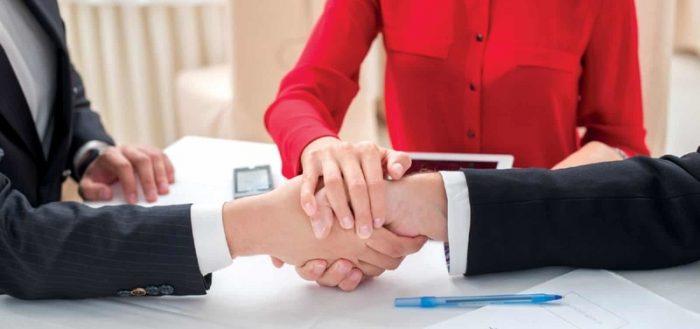 Мужчины пожимают друг другу руки за рабочим столом в присутствии женщины