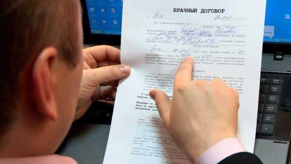 Мужчина читает брачный контракт