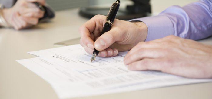 Крупным планом руки мужчины, заполняющего документ