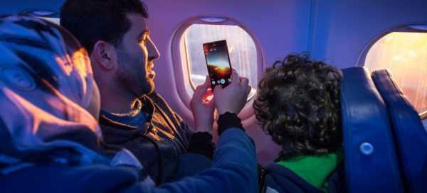 Пассажир в самолёте со смартфоне
