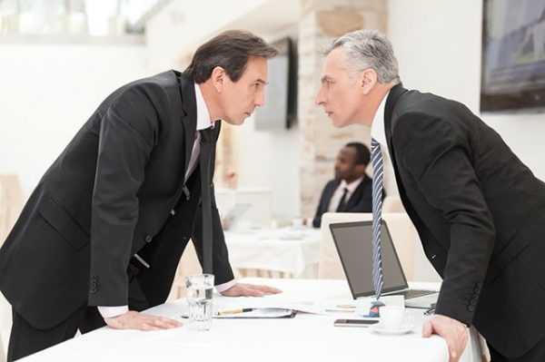 Мужчины в костюмах стоят друг против друга