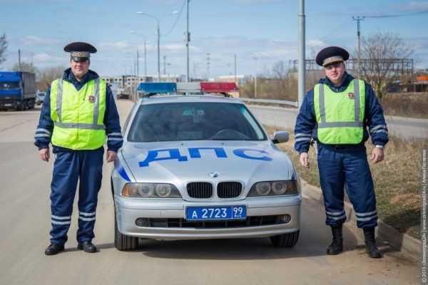 Два сотрудника ДПС у служебного автомобиля