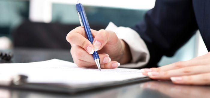 Крупным планом рука женщины, заполняющей документ