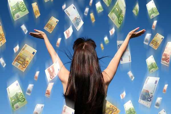 Девушка с распростёртыми руками стоит под денежным дождём