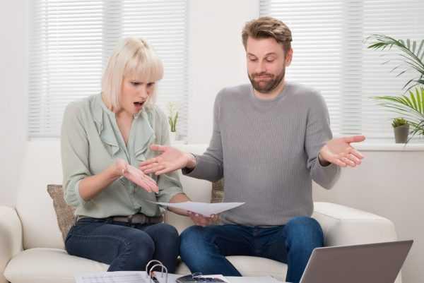 Женщина с возмущением изучает документ, а мужчина разводит руками