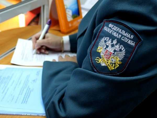 Сотрудник ФНС заполняет бумаги за столом