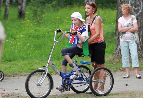 Женщина с ребёнком на велосипеде для инвалида