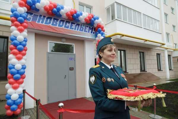 Квартирный дом, на входе в который вывешены воздушные шары и лента с надписью «С новосельем!»