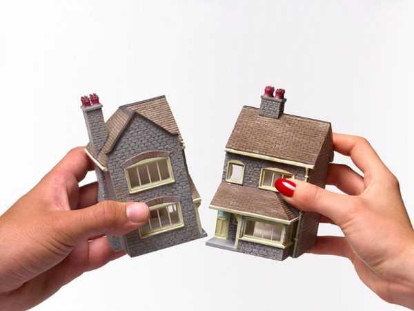 В руках у мужчины и женщины игрушечный домик, который разделён на две части