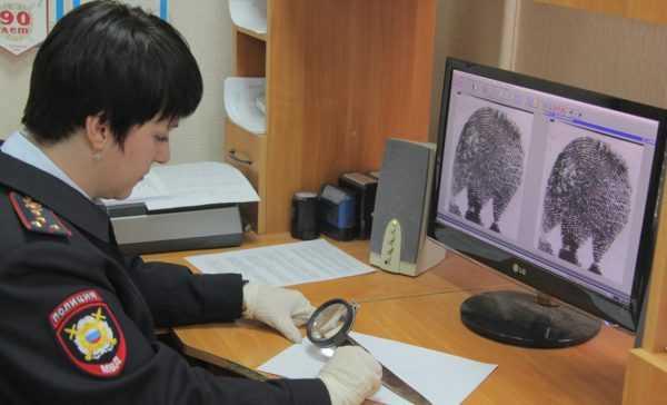 Сотрудица полиции работает с отпечатками пальцев