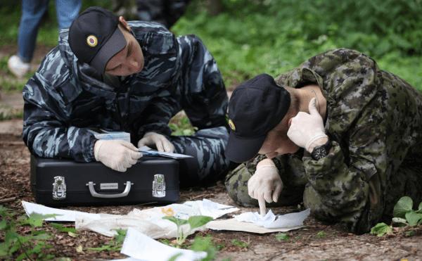 Криминалисты изучают бумаги лёжа на тропинке