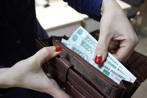 Крупным планом руки женщины, пересчитывающей деньги в кошельке