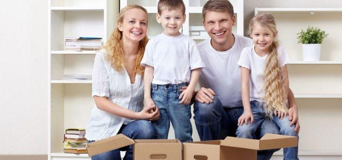 Семья с детьми разбирает коробки в новом доме