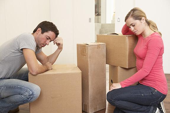 Грустные мужчина и женщина сидят у картонных коробок