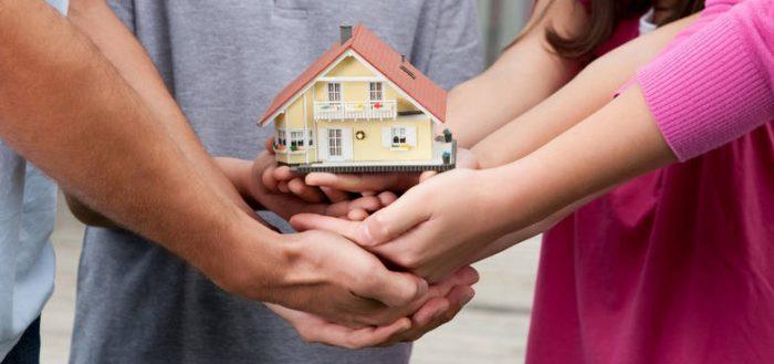 Крупным планом руки членов семьи, которые держат маленький домик