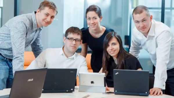 Люди сидят за столом перед компьютерами
